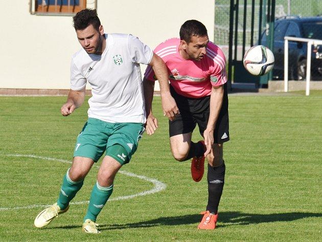 Roman Mužík v divizní dohrávce Jankova s Čížovou (1:2) bojuje s hostujícím Michalem Polodnou: o víkendu fotbalové soutěže v kraji pokračují.
