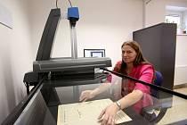 Jediným způsobem, jak uchovat staré tiskoviny i pro příští generace, je jejich digitalizace. Na snímku převádí tiskoviny do digitální podoby archivářka Martina Janků.