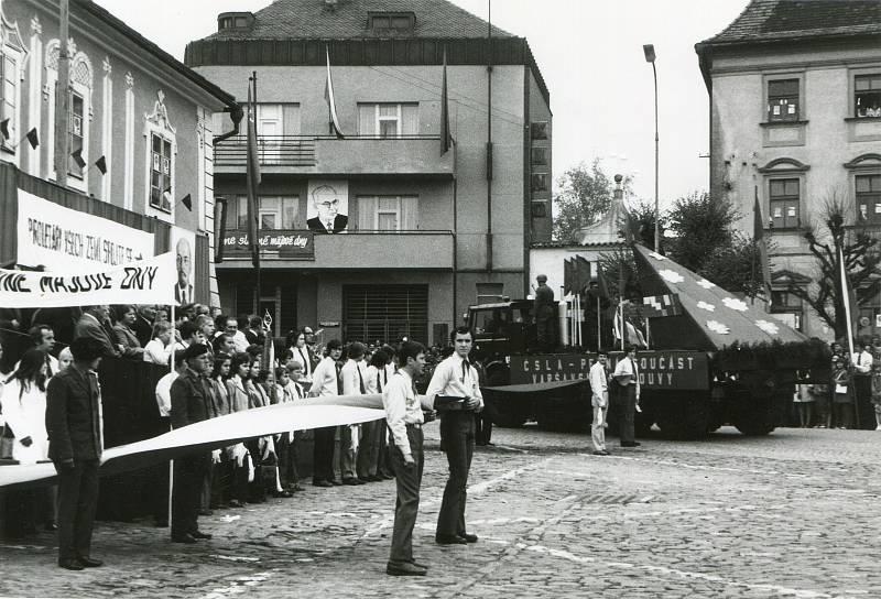 1. máj 1974. Alegorický vůz ČSLA před tribunou na náměstí, vpozadí budovy spořitelny a muzea.