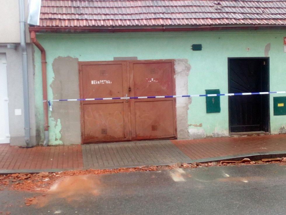 Muž před domem uklízel rozbité tašky ze střechy v Českých Budějovicích v Baarově ulici.