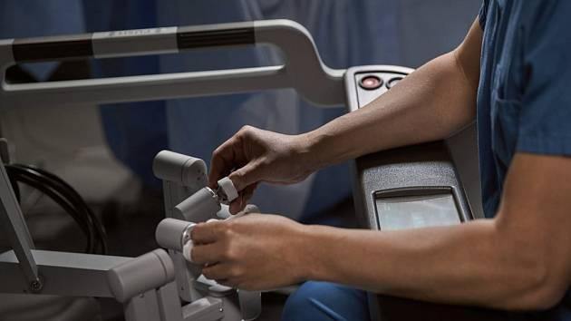 Chirurgická konzole (na snímku) – zde sedí chirurg, který ovládá na dálku pomocí speciálních prstových ovladačů tři robotické nástroje a endoskopickou kameru.