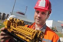 Souprava vážící 130 tun a měřící téměř 25 metrů včera přivezla do temelínské elektrárny záložní dieselgenerátor, který doplní současné náhradní zdroje elektřiny. Na snímku drží projektový manažer Pavel Krejčí model dieselgenerátoru.