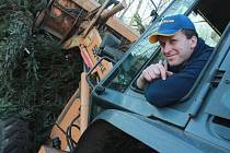 Snímek zachycuje při manipulaci s vánočními stromky ve sběrném dvoře v Dolní ulici řidiče kolového nakladače Josefa Baťhu.