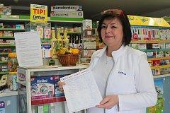 Lékárnice Renata Kašpárková s podpisy, jimiž Májští žádají o zachování lékárny.