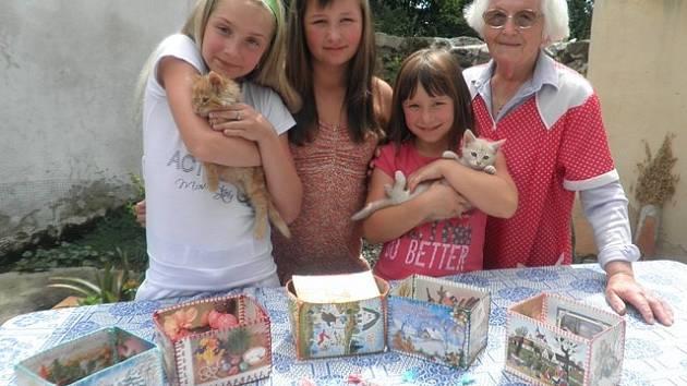 Na snímku jsou zachyceny Marie Vokůrková z Dřítně, její pravnučky Reginka, Barunka a Adélka a některé krabičky nebo knižní záložky vyrobené z pohledů.