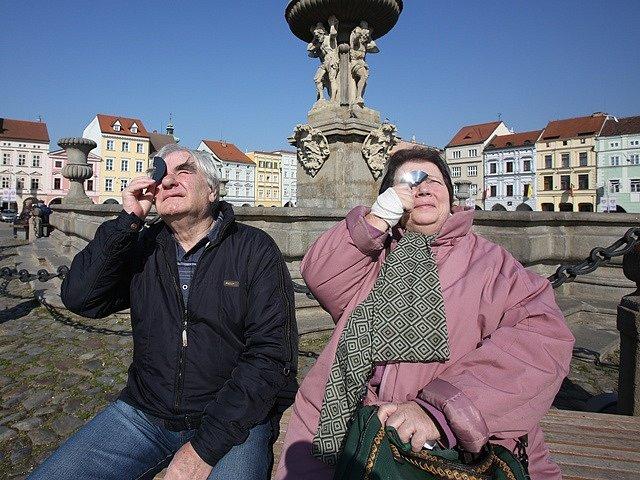 Manželé Frejlachovi sledují zatmění Slunce na českobudějovickém náměstí.