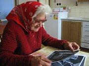 Růžena Štěpková ze Zbudova si doma ve své kuchyni prohlíží některé záběry z filmu Kam čert nemůže. Zahráli si v něm její synové.