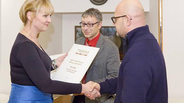 Rony Plesl přebírá cenu od Marcely Titzlové. Přihlíží tiskový mluvčí Budvaru Petr Samec.