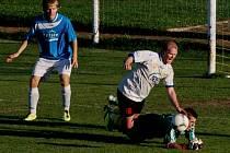 Štěpán Kuchař (na snímku padá přes sušického brankáře Karla Gilla) dal v Milevsku na 1:0 pro fotbalisty domácího ZVVZ, kteří nakonec v utkání se Sušicí vyhráli 2:0.