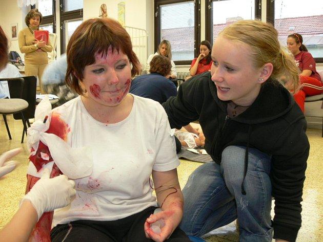 Studentky Zdravotnické školy v Českých Budějovicíh ošetřují figurantku Petru Dvořákovou z 2.A, která představuje zraněného s tepenným krvácením.