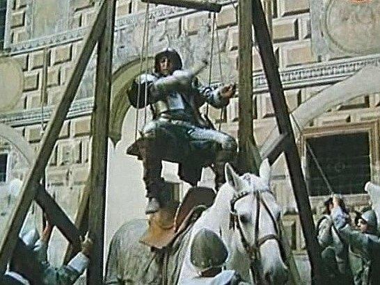 Na čtvrtém nádvoří krumlovského zámku se jede snaží dostat do sedla pomocí důmyslného zařízení.