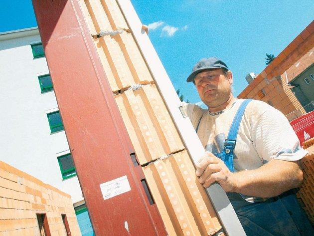 STAVENIŠTĚ. Zedník Milan Vaňous z českobudějovické stavební firmy při kontrole zdění výstavby koridoru mezi budovou interny a centrálními laboratořemi.