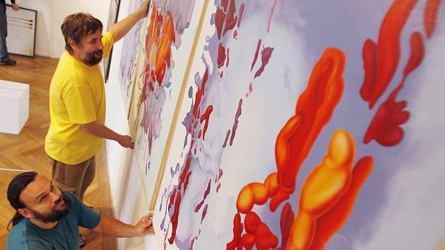Zdeněk Harazin/dole/a Luděk Stukbauer instalují Harazinovy obrazy z cyklu Bůh stvořil Zemi do interiéru sálu Jihočeského muzea v Českých Budějovicích.