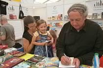 Podpis pro Amálku. Malá návštěvnice sleduje s nadšením Hynka Klimka podepisujícího díl Strašidláře Mezi námi vílami.