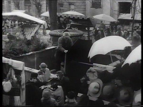 Tržiště vyrostlo ve filmu na nám. Mikuláše zHusi. Trhy se tu občas konají dodnes. Vzadu vlevo je vidět škola, vpravo vstup do kostela.