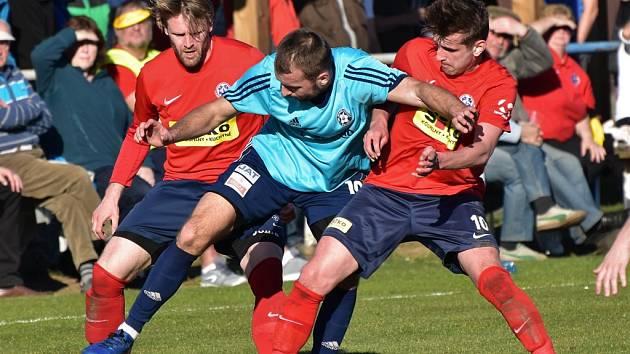 Fotbalové soutěže v kraji o víkendu pokračují. Na snímku z utkání krajského přeboru Katovice - Čimelice (1:2) je domácí Vladimír Uher mezi Mezerou a Převrátilem.