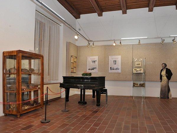 První sál po vstupu do expozice. Na klavíru leží adventní věnec. Vpozadí je silueta Hany Benešové vživotní velikosti.