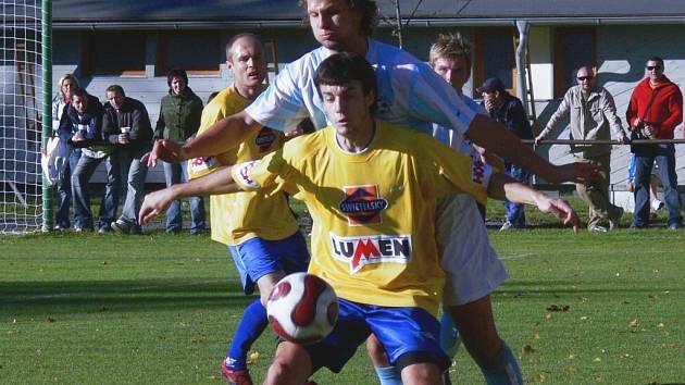 Střelec vyrovnávací branky Hluboké Lukáš Dudek si v derby kryje míč před Petrem Kadlecem.