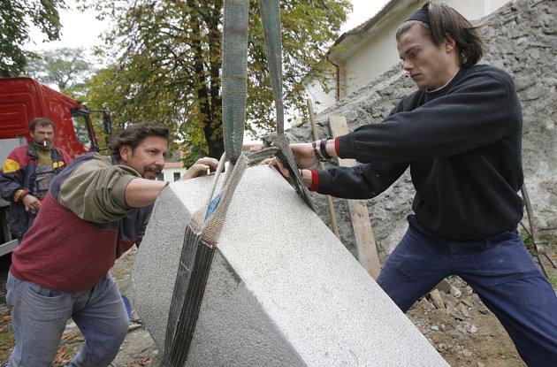 Restauratér Richard Rudovský  (vlevo) s pomocníkem Jaroslavem Králem včera osazovali nové žulové pilíře.