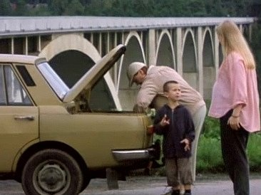 Iva Janžurová (v předklonu) dělá pořádek v kufru auta, kde se převrhla urna. Zvídavý vnuk Leonek pokládá své matce řadu otázek.
