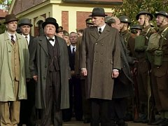 Winston Churchill (v cylindru) vykládá Edvardu Benešovi (po jeho levici), že ve válce je třeba být nemilosrdný – zabít více žen a dětí než nepřítel.