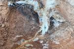 Štěrkopísek tmelený oxidy železa (oranžovo-hnědá barva) a manganu (černá barva), skrz který je po puklině proplavován jemný křemenný písek bez tmelu (bílá barva), pískovna Lžín na Soběslavsku.
