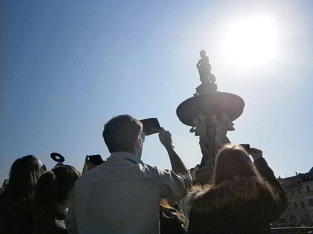 Lidé pozorují zatmění Slunce na českobudějovickém náměstí.