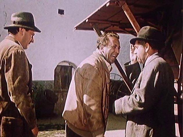Záběr z filmu Kam čert nemůže. Jiří Sovák (vlevo) a Vlastimil Brodský (vpravo) odvádějí Miroslava Horníčka dovnitř rychty U Kubatů. Vidět je i mlátička.