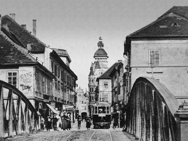 Tramvaj stojí před divadlem a před starým Zlatým mostem. Starý most neměl patřičnou nosnost, proto jezdila přes most tramvaj prázdná a cestující šli na druhou stranu pěšky.