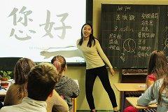 Stážistka Muying Li z Číny učí sedmáky pozdrav v čínštině. Žáci si zkoušeli napsat své jméno čínskými znaky, které se děti v Číně učí od 6 do 18 let, každý den 15 znaků.