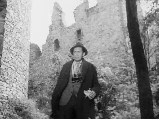 Agent Rudolf Junek vpodání Miroslava Doležala na zřícenině hradu Helfenburk ve filmu Přicházejí ztmy.