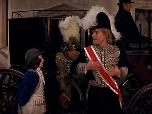 Kočár dorazil na nádvoří zámku. Právě zněho vystupují Jackie Chan a Owen Wilson (vepředu) a snimi malý pobuda.