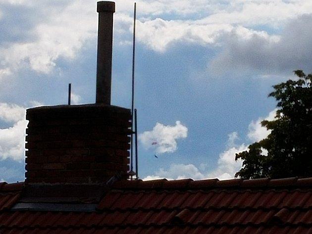 Pilot se katapultoval. Na snímku je vidět vpravo od komína.