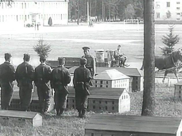 Na dvoře kasáren ve Vimperku se odehrává cvičení mezi maketami domů. Vede ho důstojník vpodání Jiřího Krampola.