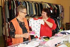 Rukama pracovnic ČČK a dobrovolnic projdou metráky použitého textilu, který využijí lidé v nouzi – od kojenců po seniory.