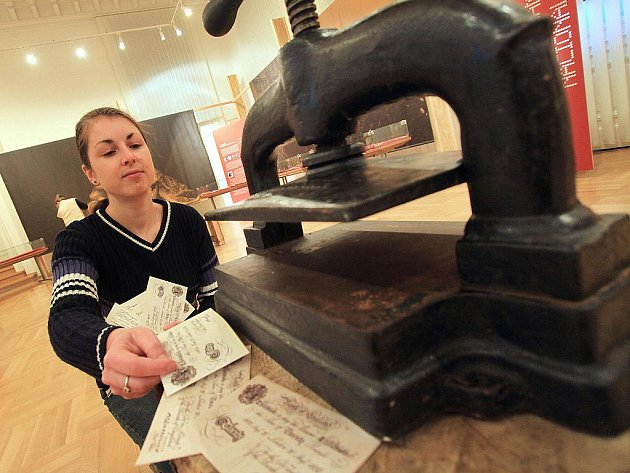 V Jihočeském muzeu začala výstava o padělání peněz. Na snímku před jedním z exponátů Eva Hyndráková, numismatička muzea.