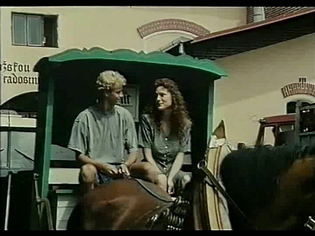 Záběr z filmu Divoké pivo. Během natáčení jezdil po městě vůz tažený koňmi a v ději distribuoval pivo. Na kozlíku s kočím seděla i Markéta Hrubešová,