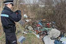 Strážník Petr Leština dokumentuje jednu z černých skládek u garáží v Husově kolonii. Další je hned o pár metrů dál.