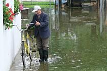 Ladislav Šustr z Plava uklízí věci ze své garáže, kterou ráno zaplavila řeka Malše. Nejen Šustr se musel ve čtvrtek poprat s několika centimetry vody na své zahrádce, když se řeka v noci ze středy na čtvrtek vylila z břehů.