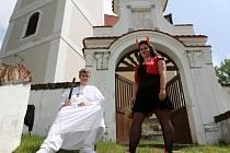 Kněz a čertice před doudlebským kostelem.