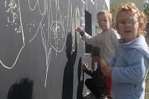 Děti z  Mateřské školky pro zrakově postižené v Českých Budějovicích mohou při hraní venku malovat barevnými křídami přímo na černé plochy zdi jedné z budov školky.