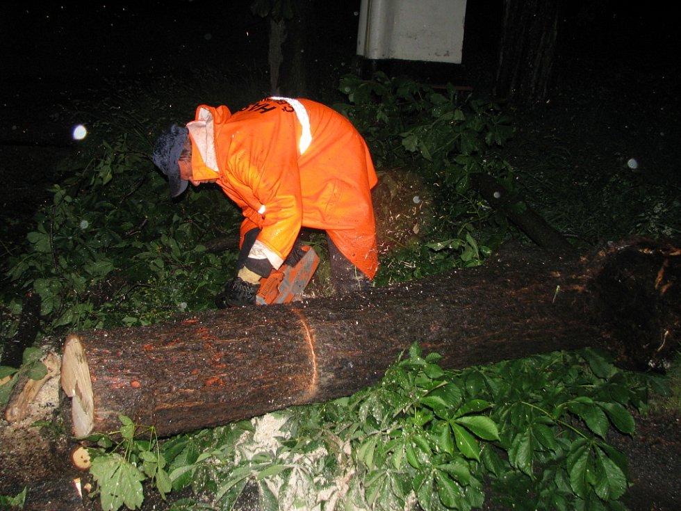 Miroslav Pečenka (s motorovou pilou) a Jiří Randák v úterý v noci likvidovali spadlý strom v Zahořicích u Boršova nad Vltavou.