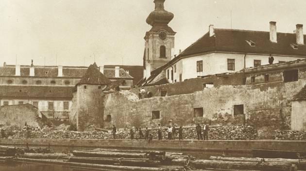 Snímek z roku 1902, kdy se bouraly českobudějovické hradby, aby vznikl prostor pro německé gymnázium. V řečišti Vltavy plavou vory s nákladem dřeva. V prostoru hradeb bývaly sklady soli.
