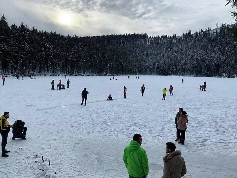 Neukáznění turisté na zamrzlé hladině Čertova jezera, které leží v Národní přírodní rezervaci. Chodit se přitom smí jen po břehu, po značených cestách.