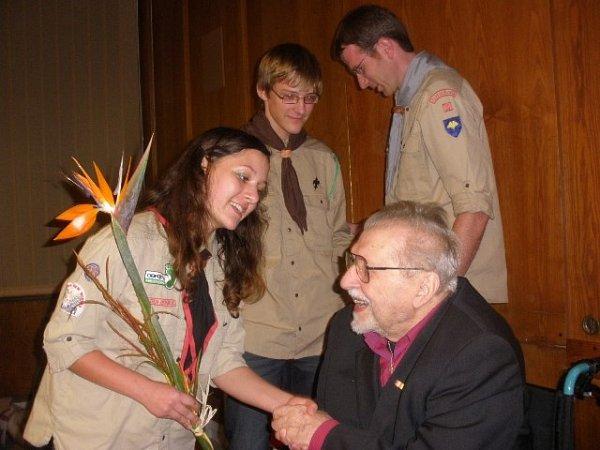 Snímek zachycuje Karla Fořta, jak mu gratulují skauti kdevadesátinám.