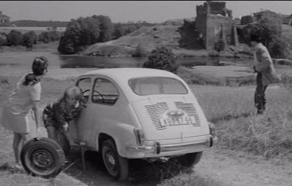 Jiřina Bohdalová a Stella Zázvorková mění ufiatky píchlou pneumatiku. Vzadu se tyčí hrad, pod ním je rybník.