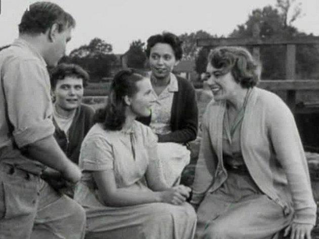 Jiřina Jirásková (na snímku vzadu v bílých šatech a tmavém svetru) hraje jednu z venkovských dívek. Právě se jde zpívat.