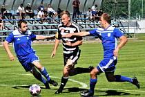 Tadeáš Bečvář se snaží proklouznout mezi dvěma hráči hostí: Dynamo B- Soběslav ve fotbalové divizi 1:0.
