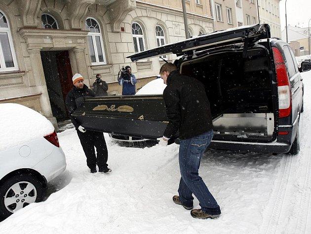 Pracovnci pohřební služby vynášejí těla obětí, ihned poté, co krimilanlisté před polednem dokončili jejich ohledání.
