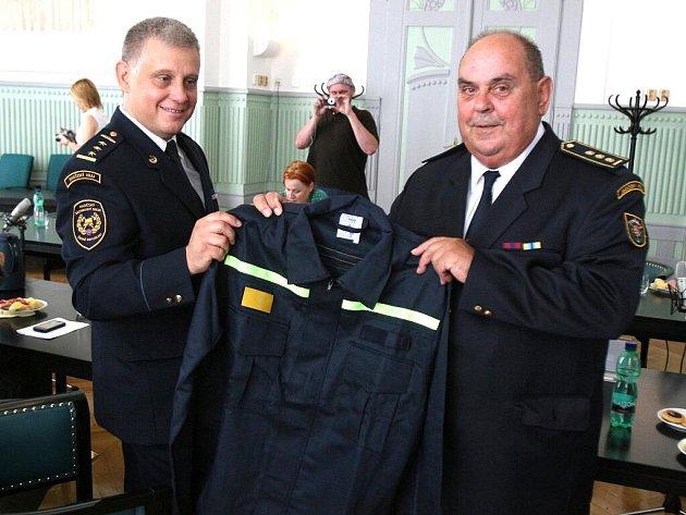 Ředitel jihočeských profesionálních hasičů Lubomír Bureš (vlevo) s Jiřím Novákem si prohlížejí dárek  od hejtmana Karlovarského kraje.